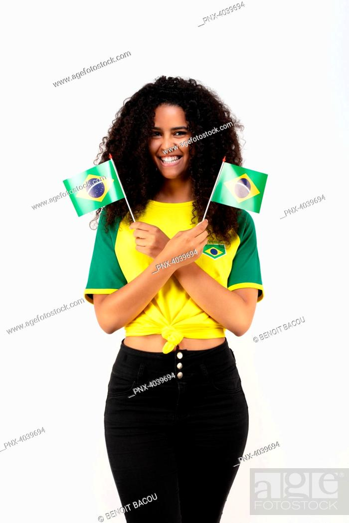 Stock Photo: Portrait of a young supporter of the Brazil team holding two small flags.