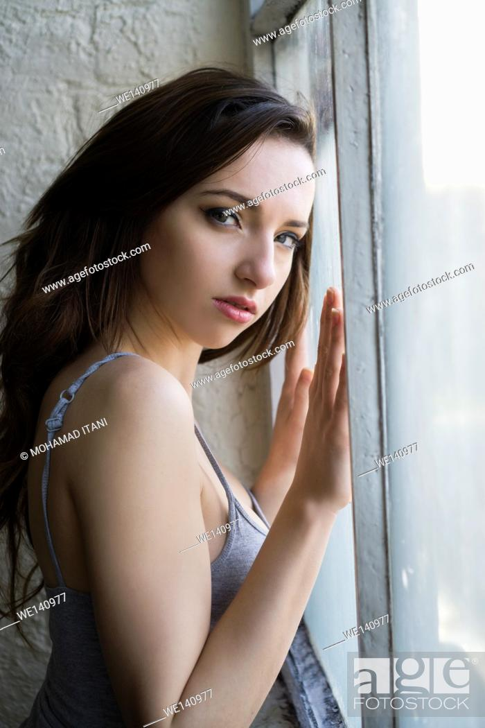 Stock Photo: Beautiful young woman hands against the window.