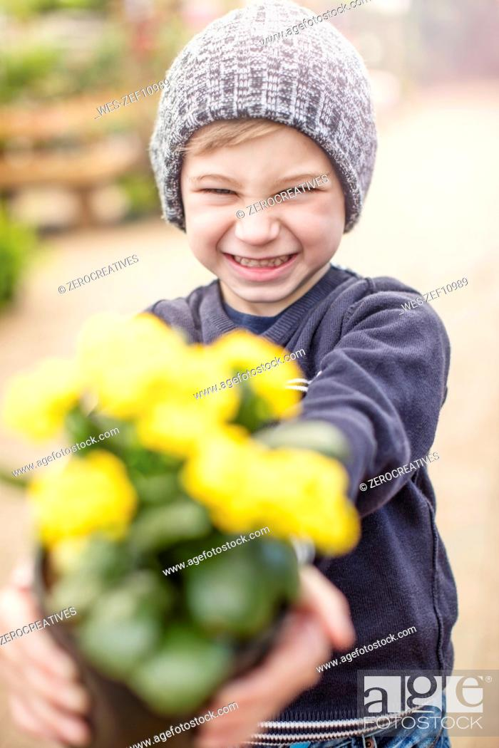 Stock Photo: Boy holding yellow flower pot.
