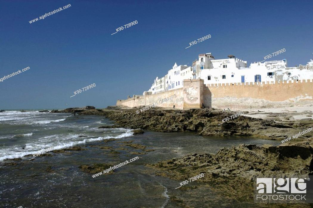 Stock Photo: View of the impressive portugese fortification of Essaouira with the surf of the Atlantic Ocean and the white washed buildings and blue doors and window frames.
