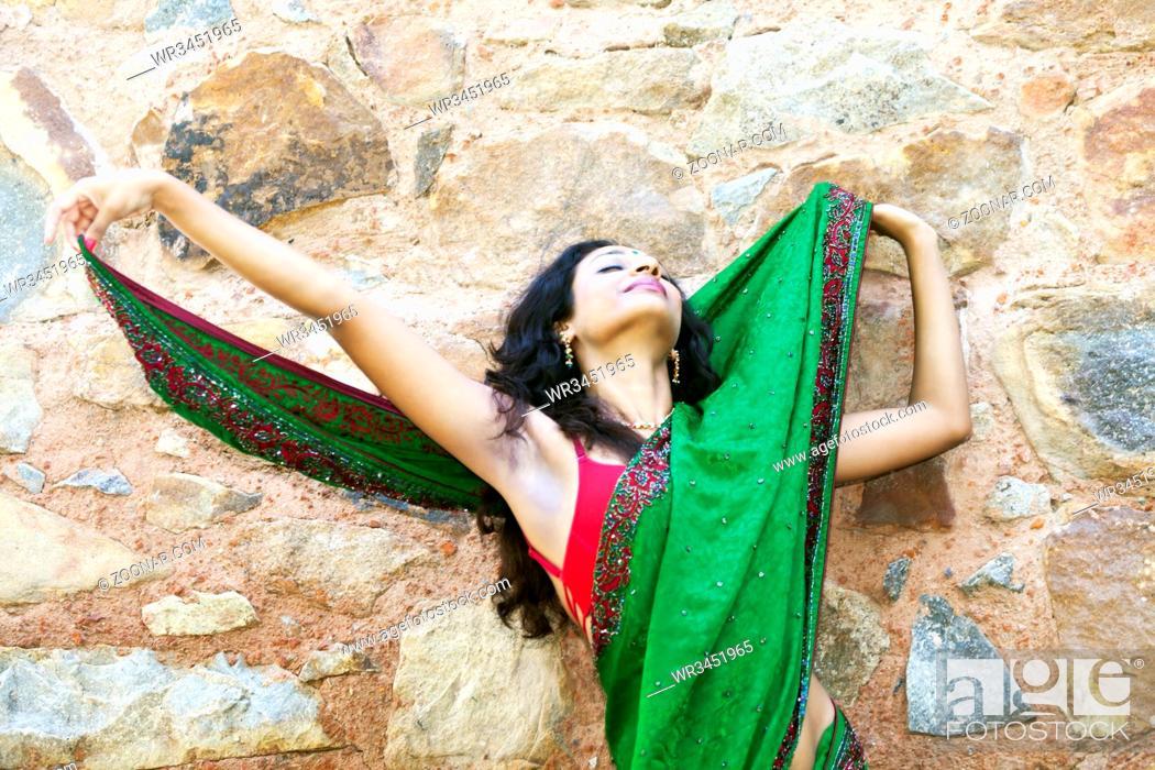 Stock Photo: indische Frau in einem Saree an einer Steinwand.