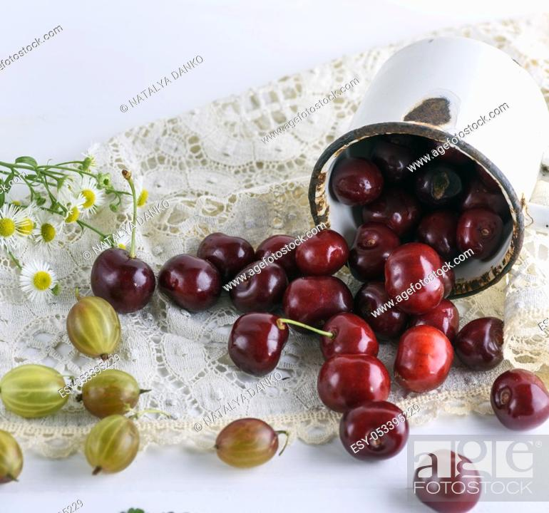 Stock Photo: scattered ripe red berries cherries from a white iron mug on a table.