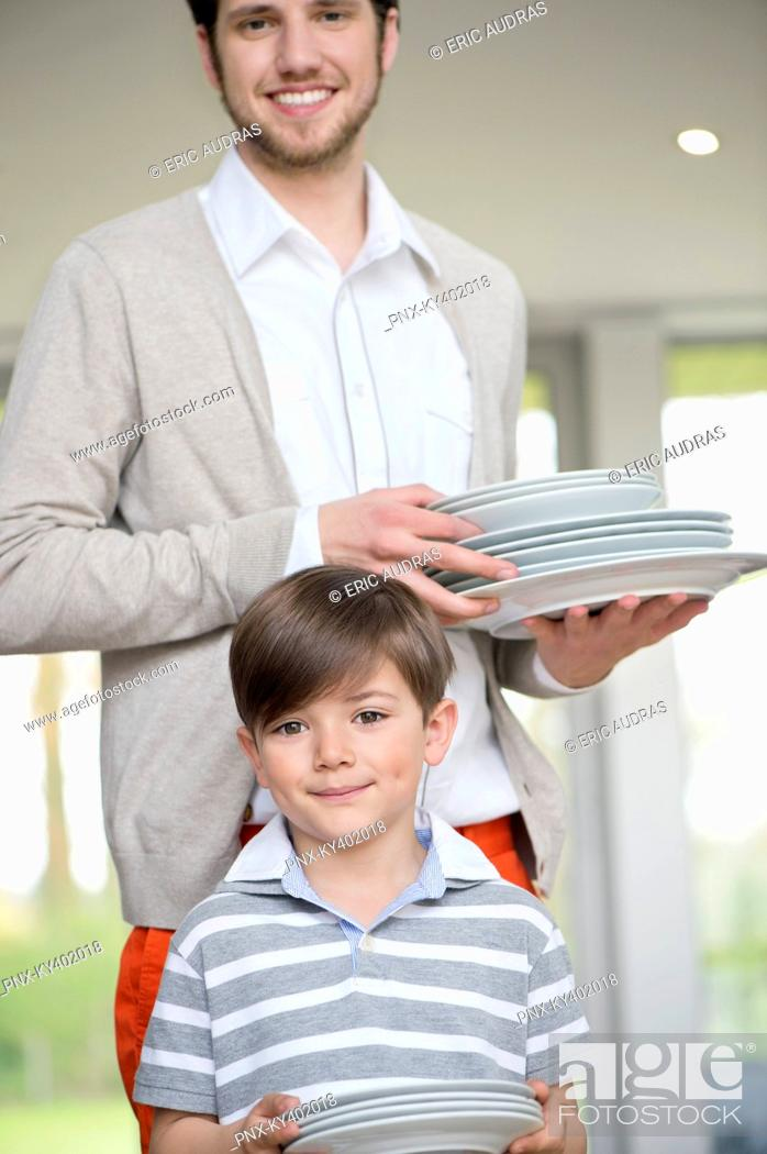 Stock Photo: Man and son arranging plates for lunch.