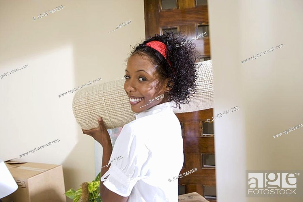 Stock Photo: Woman moving house, carrying rolled-up carpet on shoulder in doorway, smiling, side view, portrait.