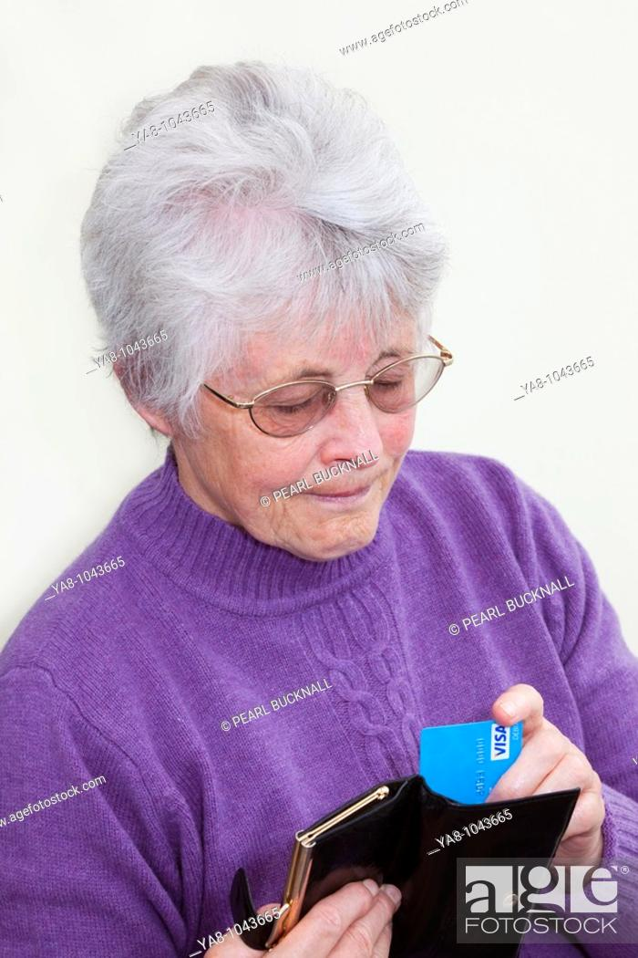 Stock Photo: Britain UK Europe  Senior woman pulling a Visa credit card from a purse looking serious MR 09/06.