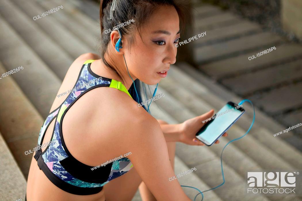 Stock Photo: Woman sitting on steps wearing earphones holding smartphone.