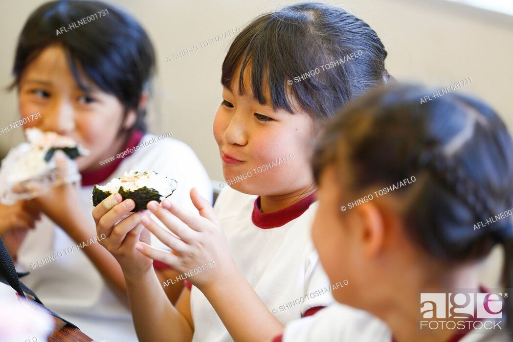Stock Photo: Japanese elementary school kids eating in the classroom.
