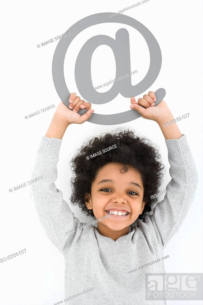 Stock Photo: Boy holding an at symbol.