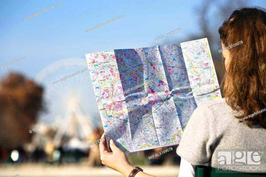 Stock Photo: Woman looking at map with Place de la Concorde, big wheel in background, Paris.