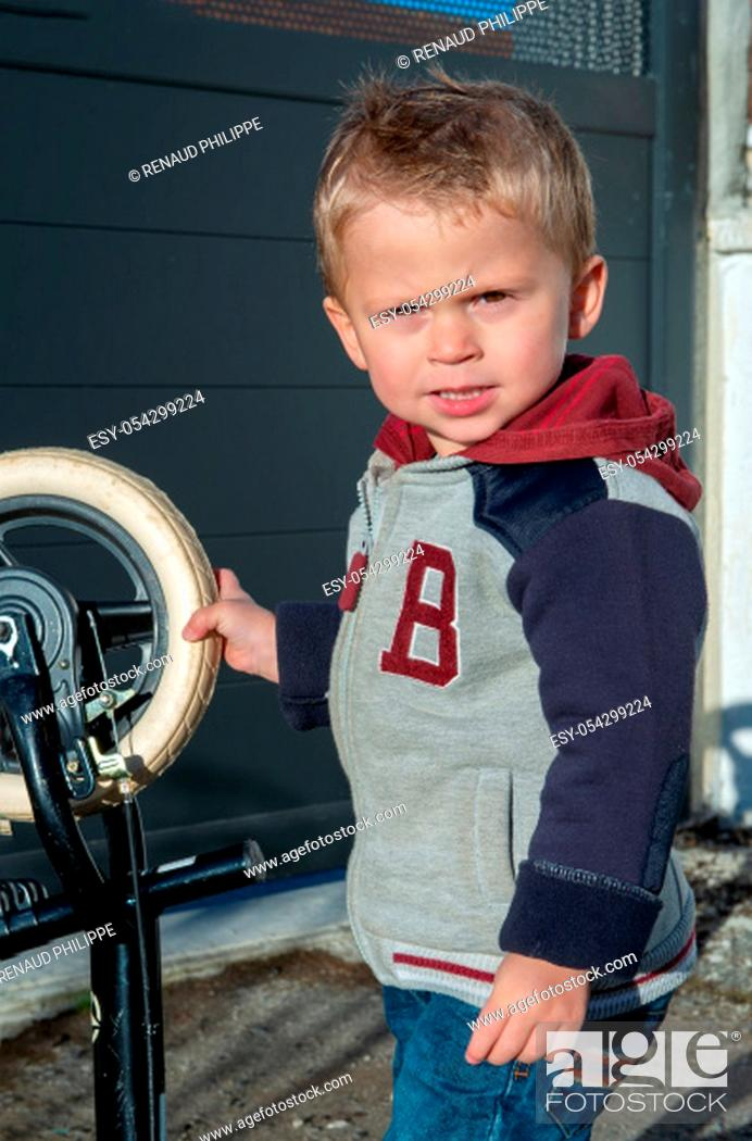 Stock Photo: cute child two years old playing with a bicycle.