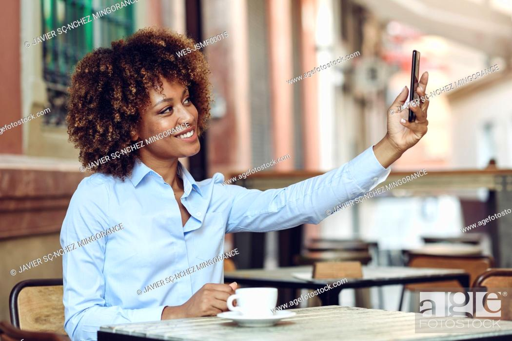 Stock Photo: Smiling woman with afro hairstyle sitting in outdoor cafe taking a selfie.