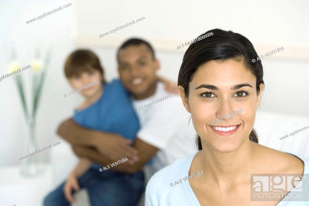 Stock Photo: Woman smiling at camera, husband and son embracing in background.