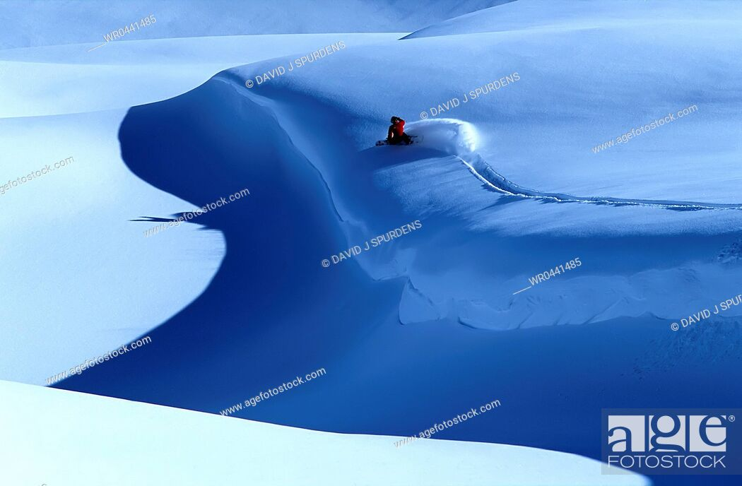 Stock Photo: A snowboarder carving deep fresh powder snow sends up a plume of snow.