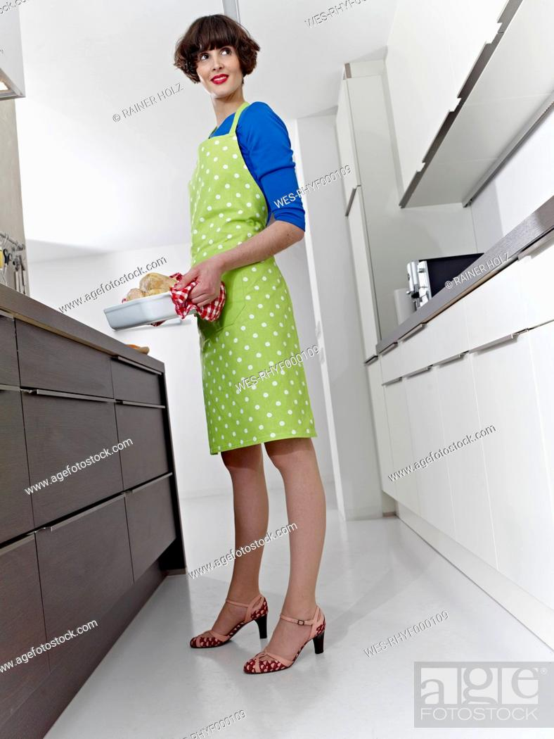 Stock Photo: Germany, Cologne, Young woman with roasted chicken in kitchen.