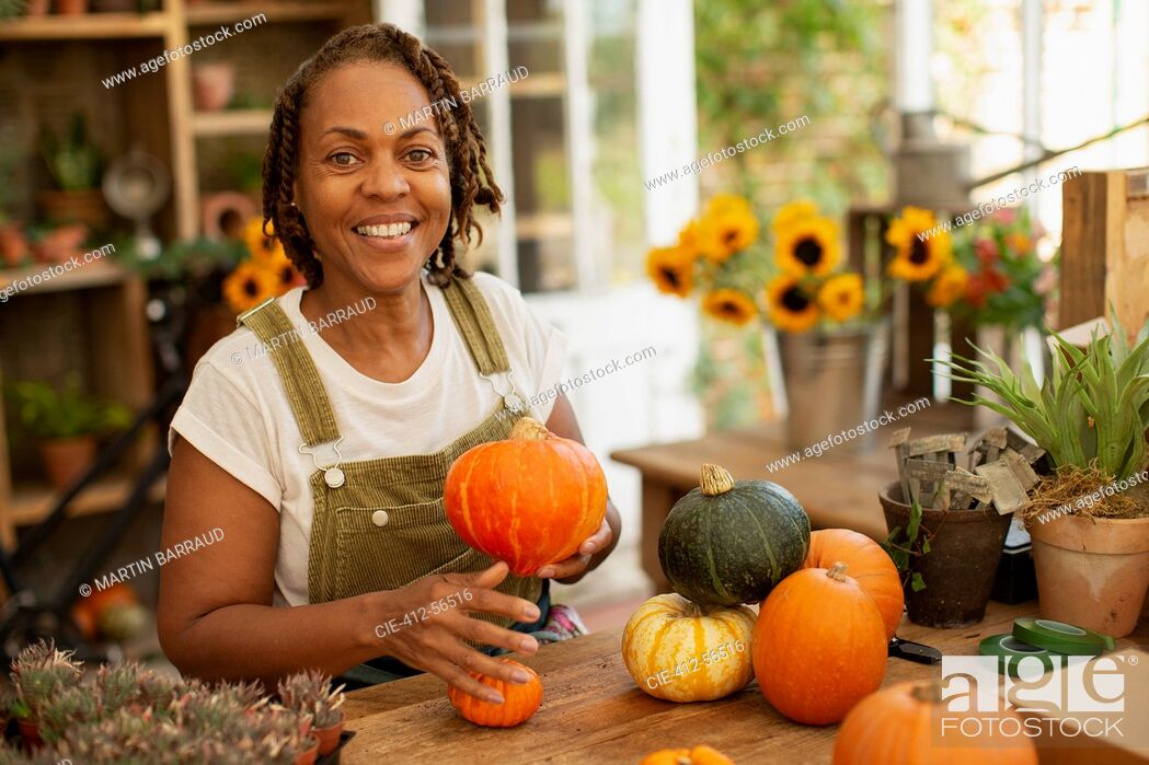 Stock Photo: Portrait happy female florist arranging autumn pumpkins in shop.