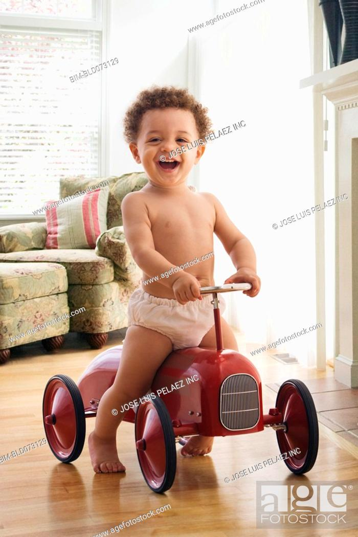Stock Photo: Mixed race boy riding on old-fashioned toy car.