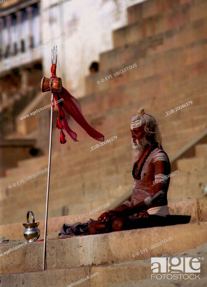 Stock Photo: Sadhu meditating in the early morning sun on the ghats of the River Ganges.