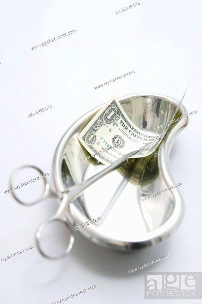 Stock Photo: Surgical scissors with a dollar in a bedpan.