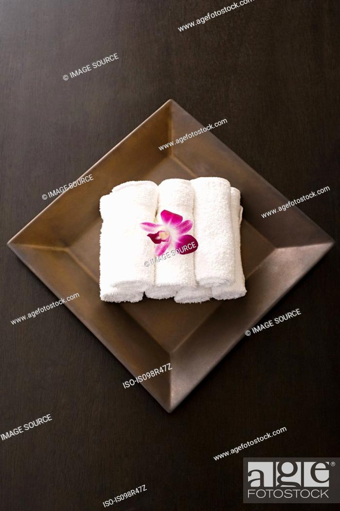 Stock Photo: Rolled up towels and orchids.