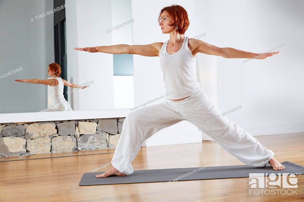 Photo de stock: Yoga Warrior two II pose exercise in wooden floor gym and mirror indoor.