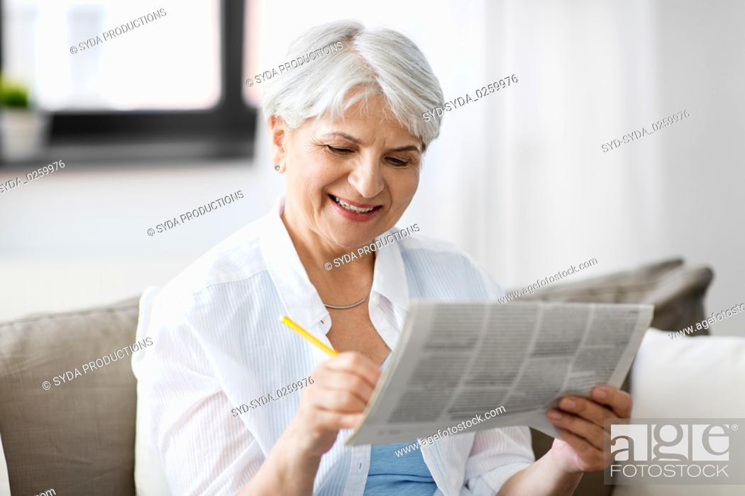 Stock Photo: senior woman marking newspaper ad at home.
