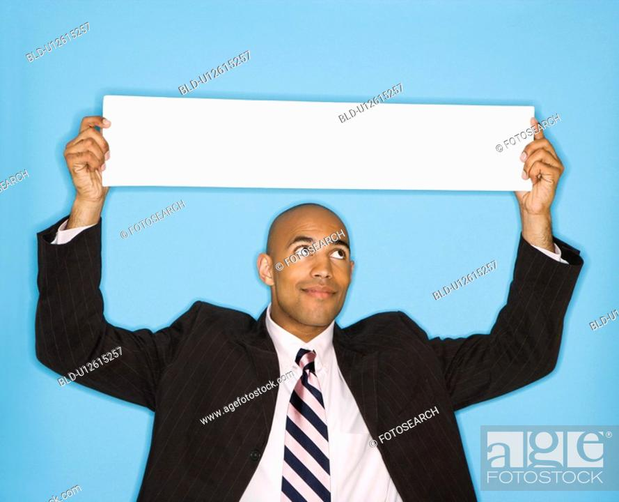 Stock Photo: Man holding blank sign against blue background.