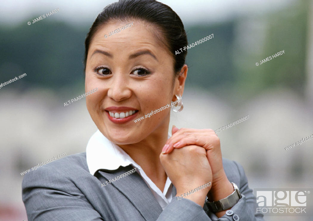 Stock Photo: Woman smiling, hands together, portrait.