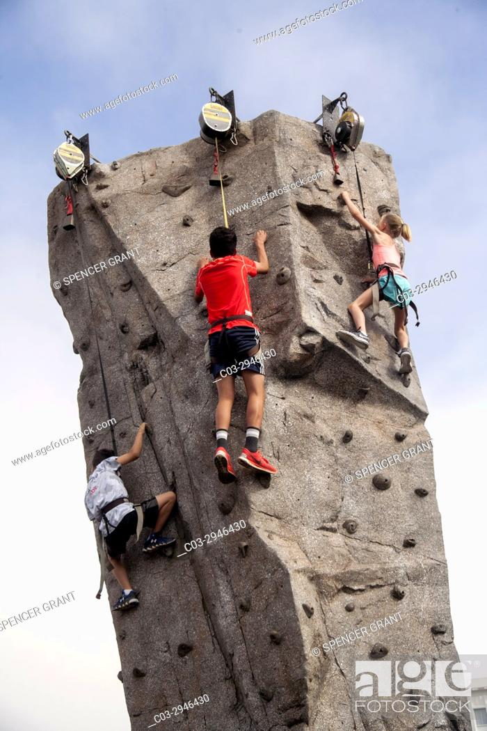 Stock Photo: Wearing safety harnesses attached to torque reels, children climb an artificial rock needle at a festival in Newport Beach, CA.