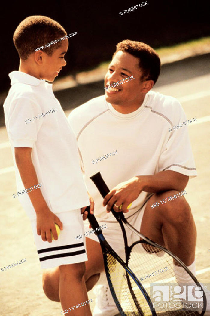 Stock Photo: Father and son in tennis outfits holding rackets.