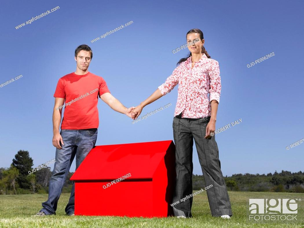 Stock Photo: Couple holding hands over small model house.