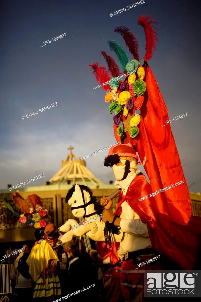 Stock Photo: A pilgrim from Tomatlan, Veracruz state, dressed as Saint James apostle performs the Baile de los Santiagos or Saint James's Dance riding a toy horse outside of.