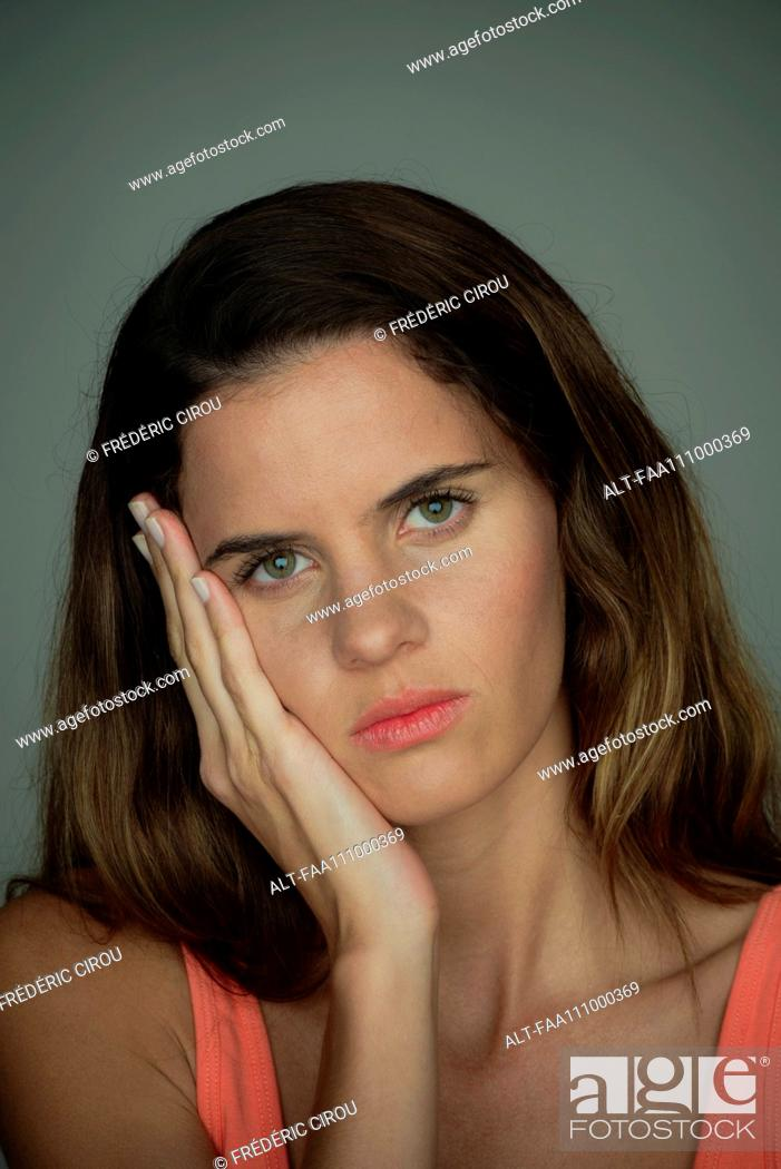 Stock Photo: Young woman resting face on hand, portrait.