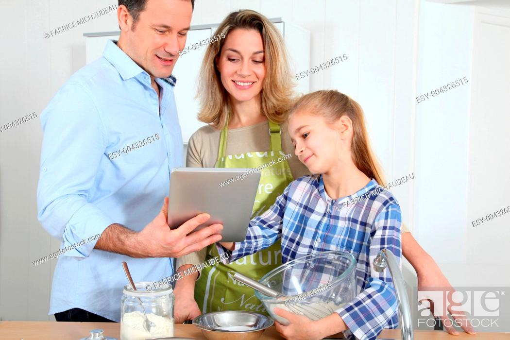 Stock Photo: Parents and daughter preparing meal in home kitchen.