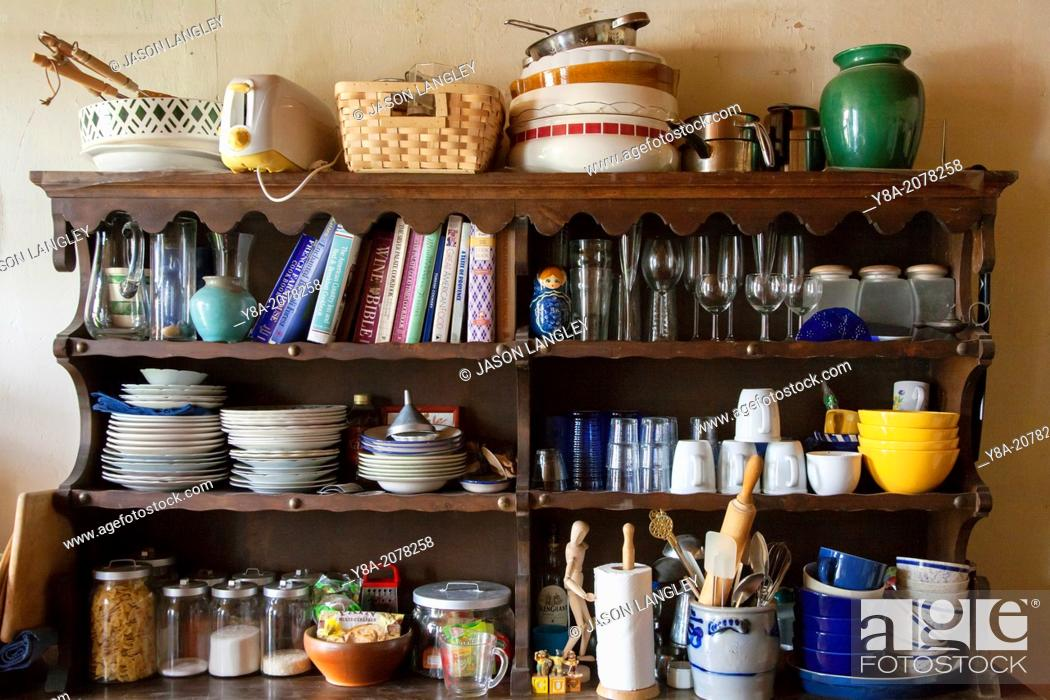 Stock Photo: Messy shelves in kitchen full of cookbooks, food, and dishes.