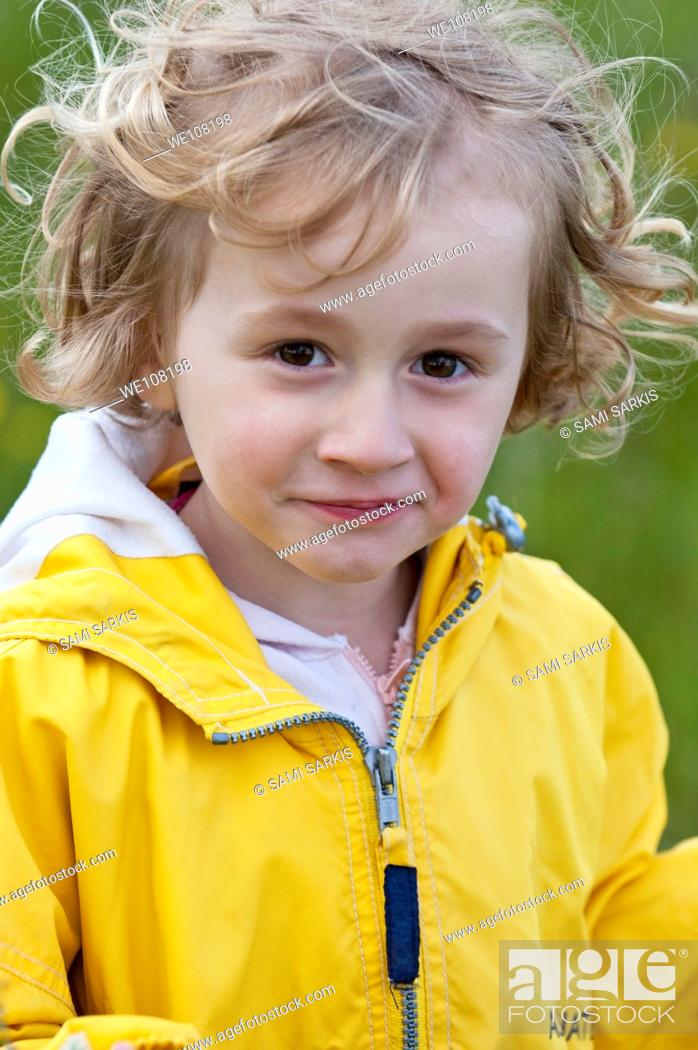 Stock Photo: Little girl wearing a yellow raincoat, Provence, France.