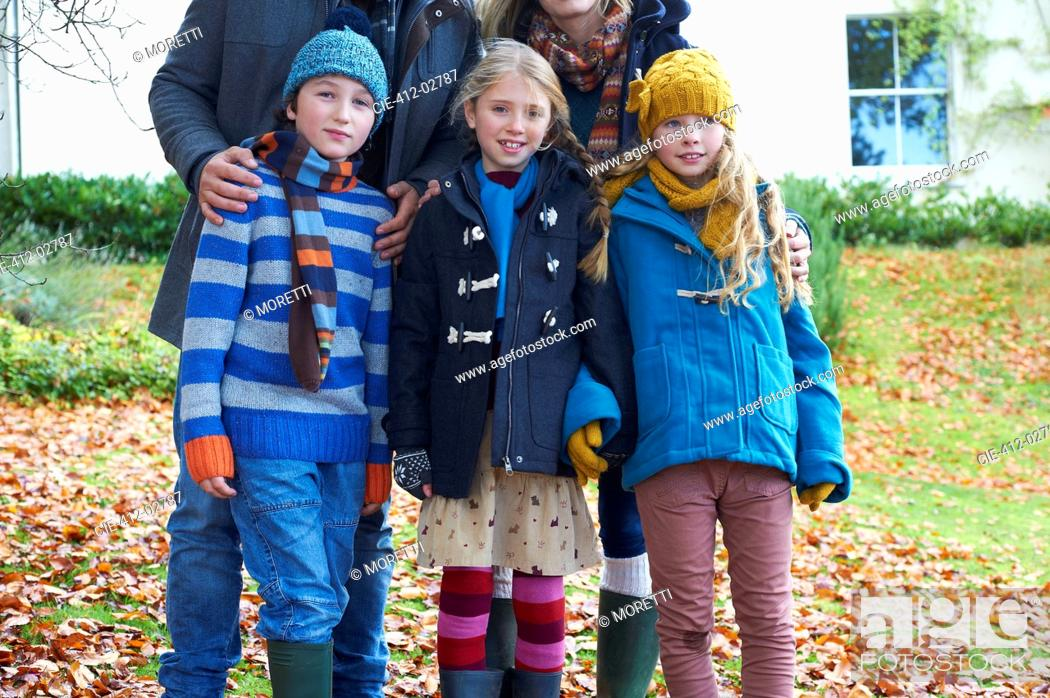 Stock Photo: Children smiling together in autumn leaves.