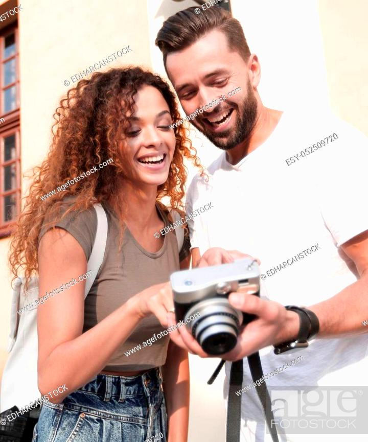 Stock Photo: Portrait of young couple walking looking at the photos.