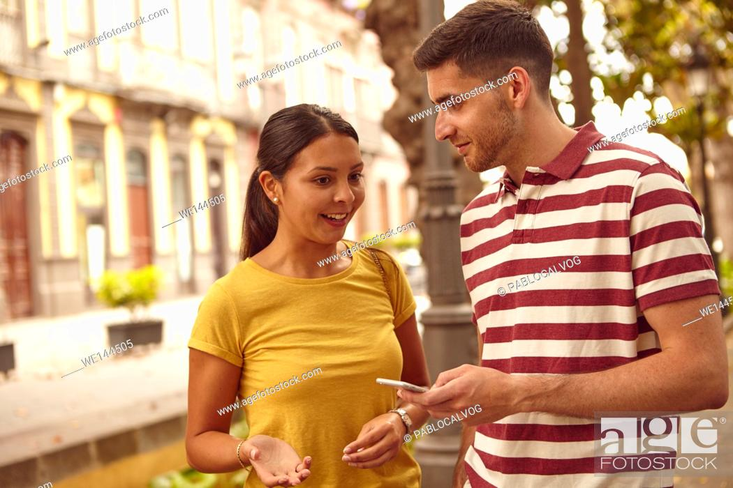 Stock Photo: Young couple looking at each other and talking with a cell phone and making hand signs while dressed casually in jeans and t-shirts.