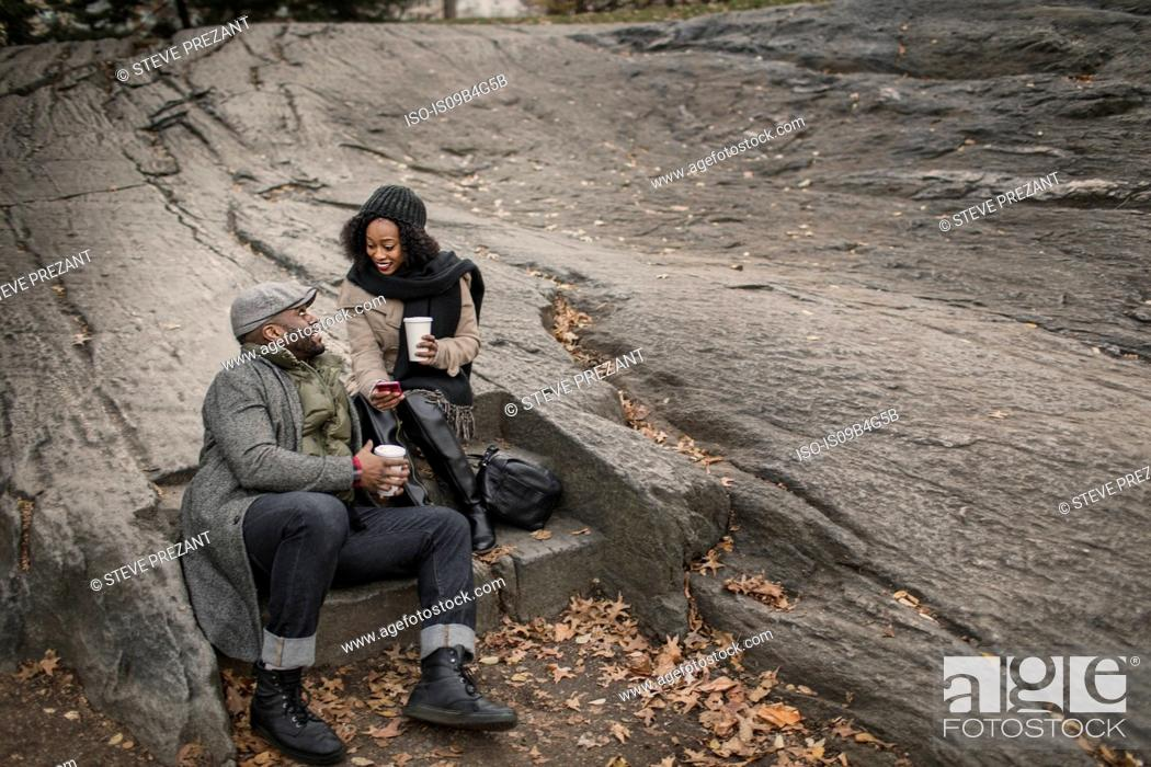 Stock Photo: Couple sitting on step in park with takeaway coffee.