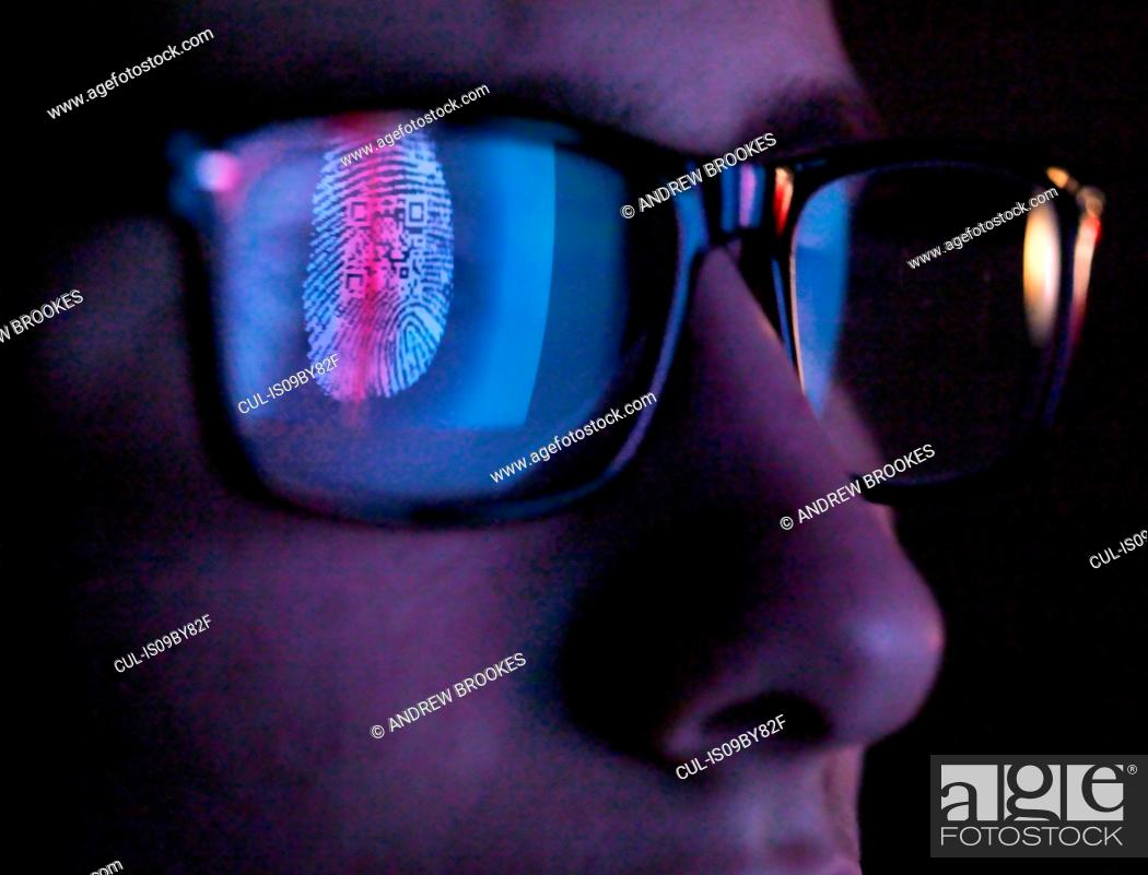 Stock Photo: Cyber Security, reflection in spectacles of access information being scanned on computer screen, close up of face.