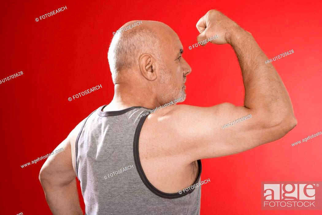 Stock Photo: Senior man flexing muscles.