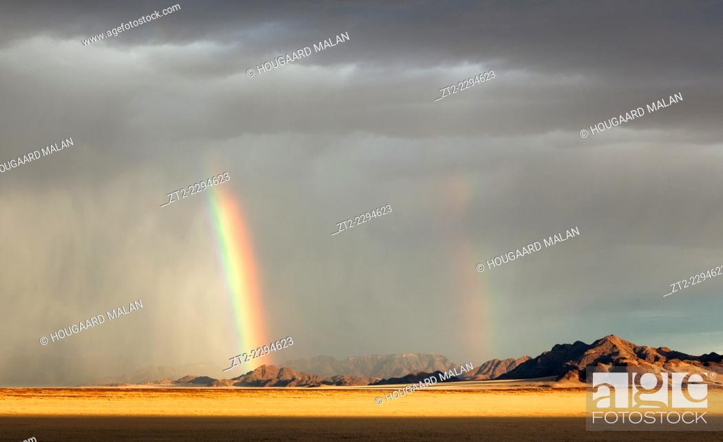 Stock Photo: Landscape photo of a rain storm pouring out over the mountains east of Sossusvlei. Sossusvlei, Namib Naukluft National Park, Namibia.