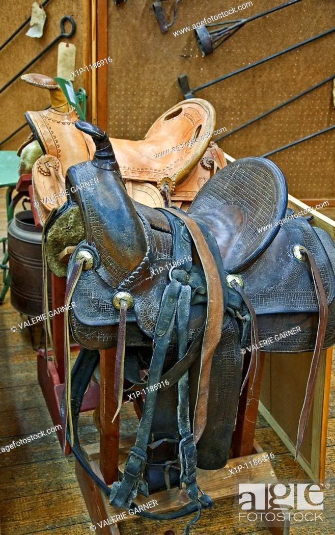 Stock Photo: This veritcal image depicts two retro leather horse saddles, one brown and the other a light tan color, on sawhorses with various iron brands in the background.