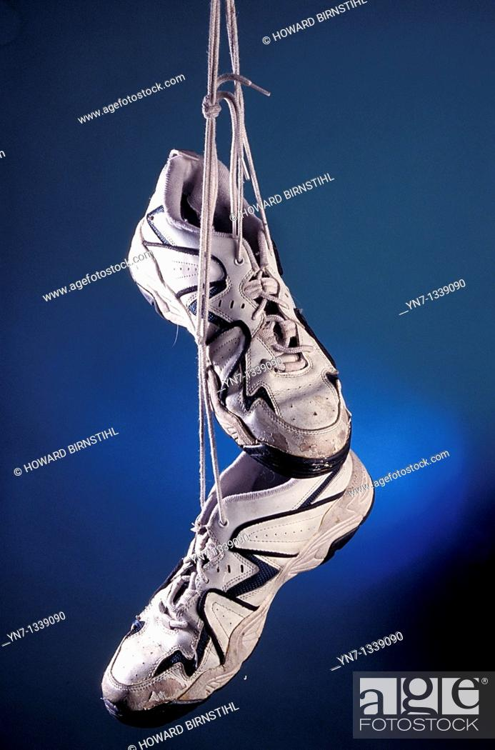 Stock Photo: a product shot of old well used running shoes on a glowing blue background.