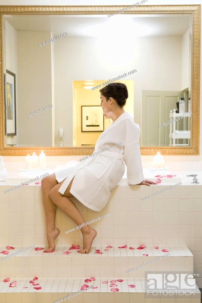 Stock Photo: Woman sitting next to bubble bath.