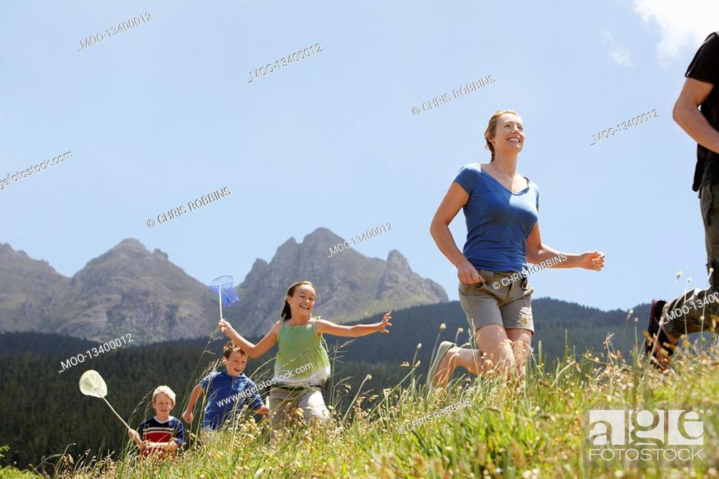 Stock Photo: Three children 7-9 holding butterfly nets running through field with parents low angle view.