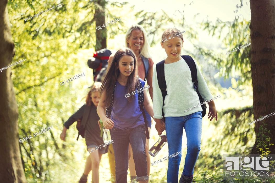 Stock Photo: Mother and daughters hiking in woods.