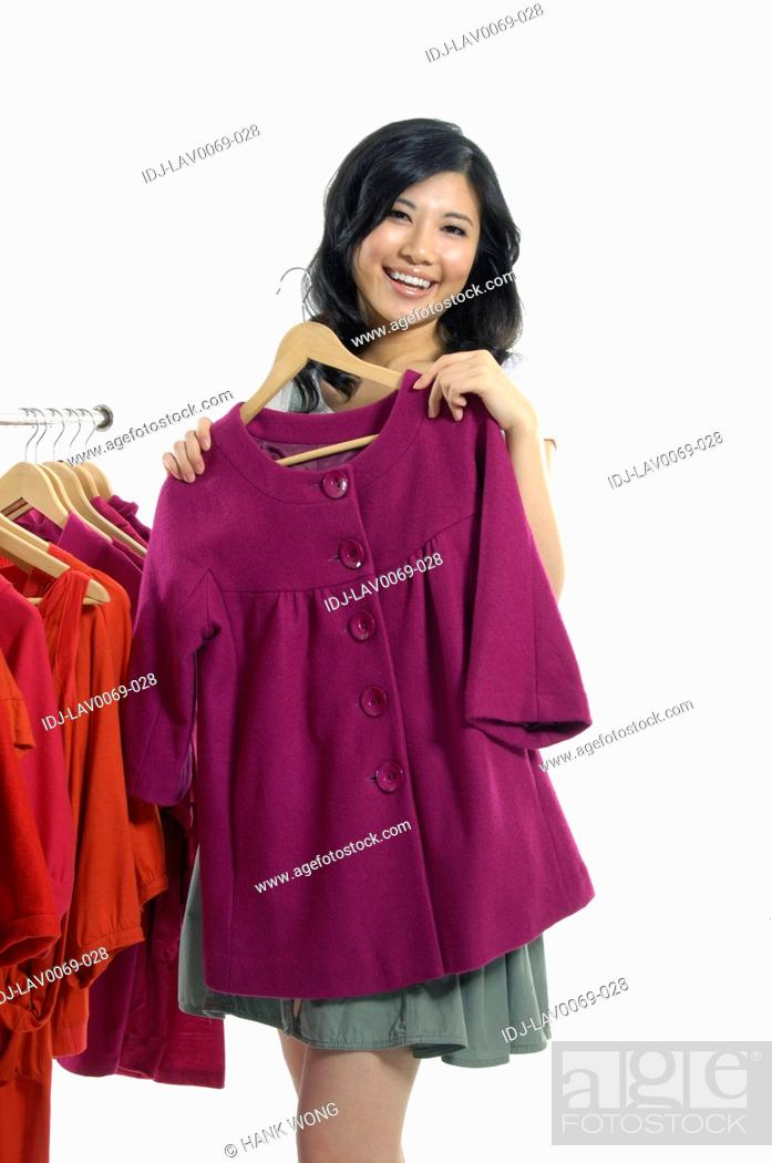 Stock Photo: Woman holding a coat in a clothing store.