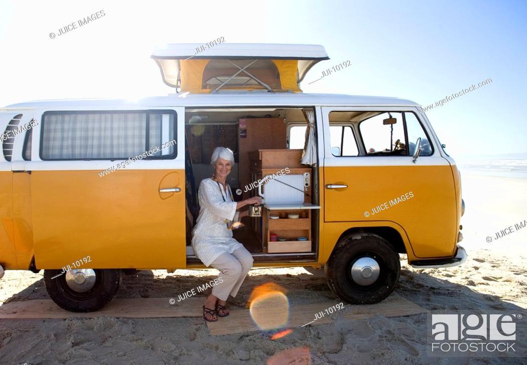 Stock Photo: Senior woman making tea in camper van on beach, smiling, portrait lens flare.