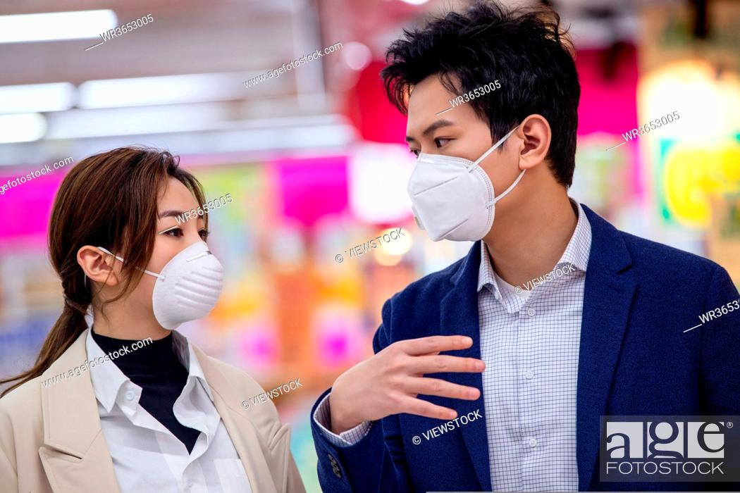Stock Photo: The young couple wearing a mask in the supermarket shopping.